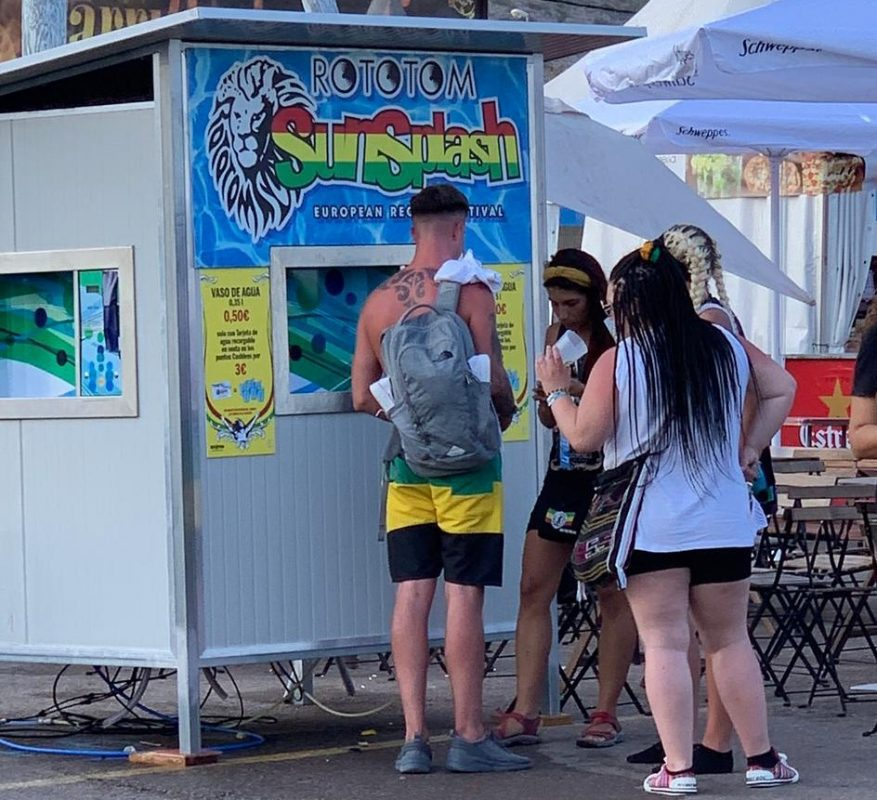 Unge mennesker fylder drikkekrus hos wetaps vandposte