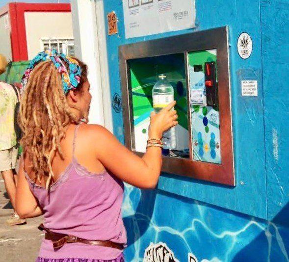 Pige fylder sin vandflaske til festival ved wetaps vandposte