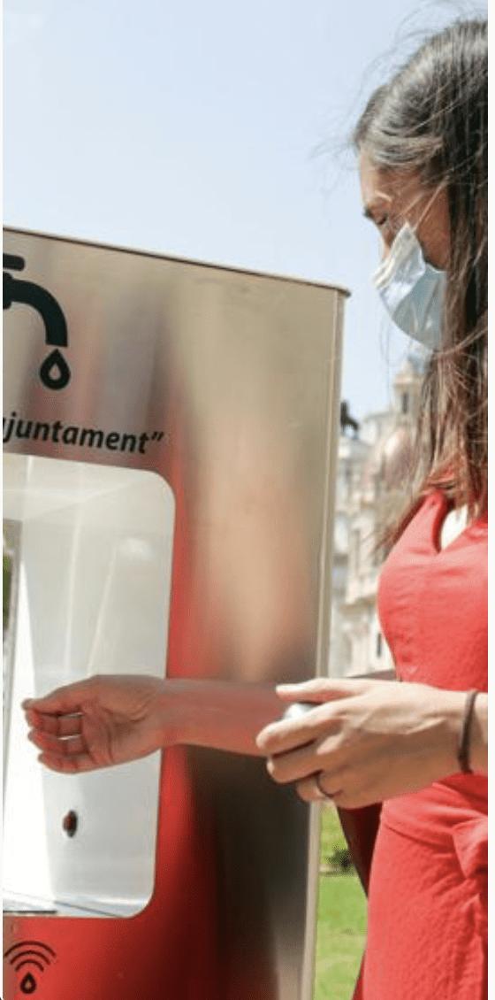 Pige tapper vand ved drikkefontæne